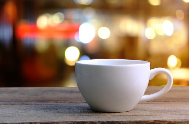 Tazza di caffè macchiato sulla tavola di legno nel fondo della sfuocatura della caffetteria. Foto Premium