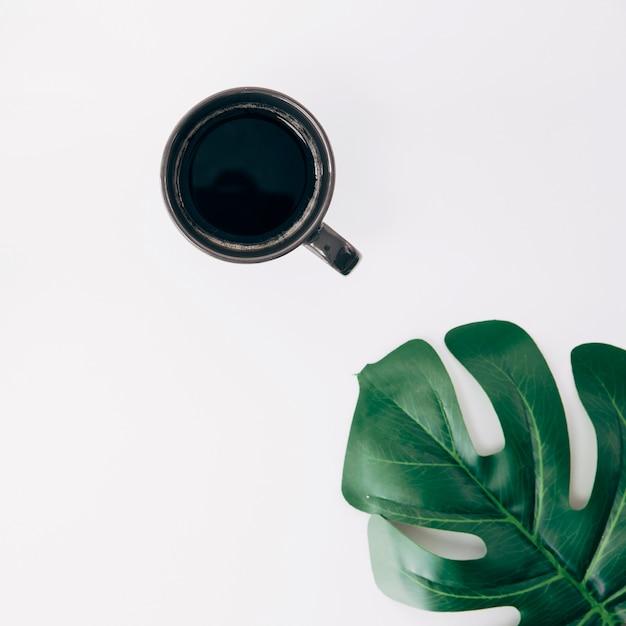 Tazza di caffè nera e foglia verde di monstera su fondo bianco Foto Gratuite