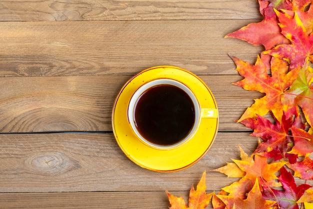 Tazza di caffè nero caldo su un tavolo di legno con foglie gialle, arancioni e rosse cadute autunno Foto Premium