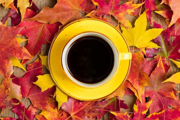 Tazza di caffè nero caldo su un tavolo di legno con foglie gialle, arancioni e rosse cadute in autunno Foto Premium