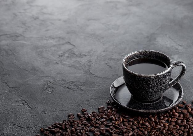 Tazza di caffè nero con piattino e chicchi di caffè freschi sul tavolo da cucina in pietra nera. Foto Premium