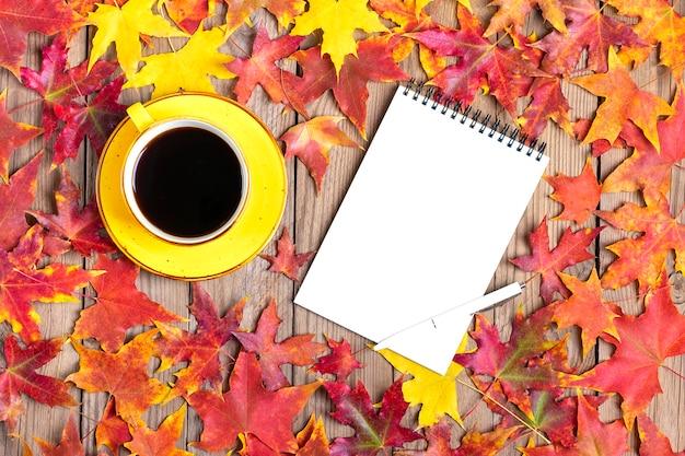 Tazza di caffè nero, lecca lecca gialla, amaretti, blocco note, tavolo in legno con foglie di autunno cadute in autunno piatto disteso Foto Premium