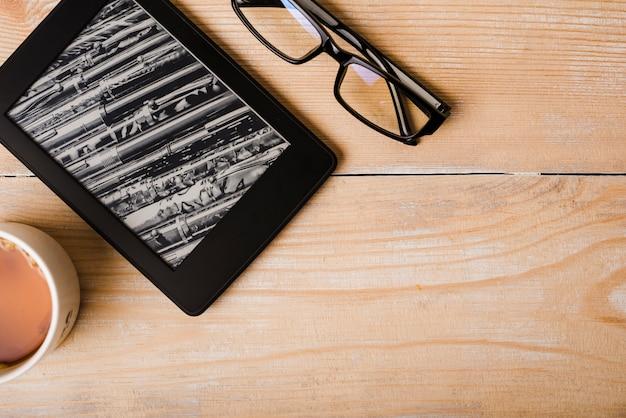 Tazza di caffè; occhiali e lettore di ebook sulla scrivania in legno Foto Gratuite