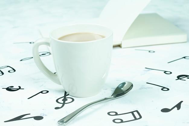 Tazza di caffè posizionata sul pavimento, modello di nota musicale Foto Premium