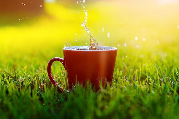 Tazza di caffè rossa su erba nel parco Foto Premium