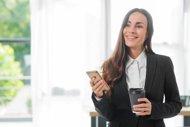 Tazza di caffè sorridente della tenuta della donna di affari e tazza di caffè eliminabile Foto Gratuite