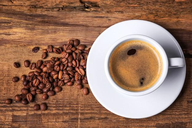 Tazza di caffè su un tavolo di legno. sfondo scuro Foto Gratuite