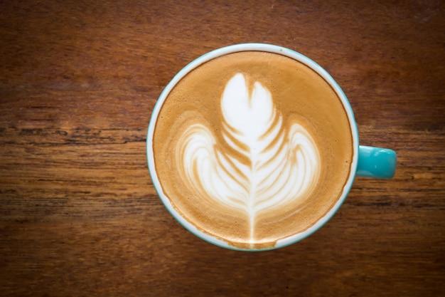 Tazza di caffè sul tavolo di legno. latte art a forma di foglia