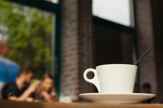 Tazza di caffè sulla tabella sopra priorità bassa defocused del self-service Foto Gratuite