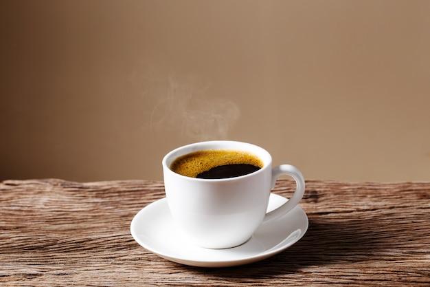 Tazza di caffè sulla vecchia tavola di legno con crema Foto Premium