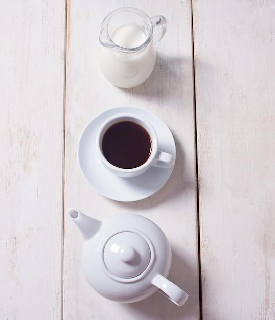 Tazza di caffè, teiera e brocca con latte in fila Foto Premium