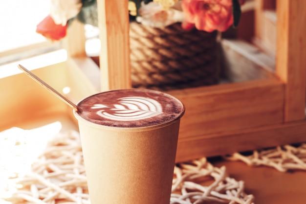 Tazza di cappuccino con un motivo su un tavolo in un caffè Foto Premium