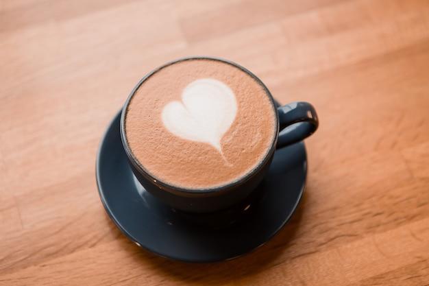 Tazza di cappuccino nella caffetteria su un tavolo di legno Foto Premium