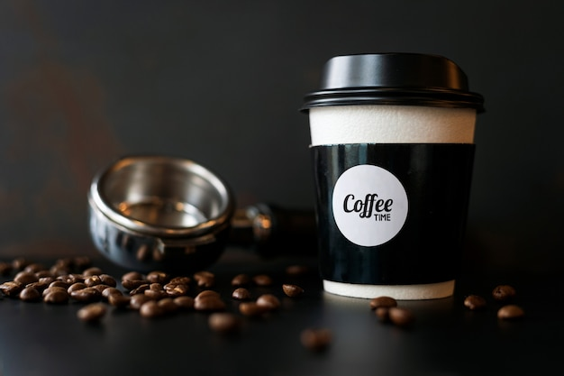 Tazza di carta del primo piano e chicco di caffè sulla tavola nera Foto Premium