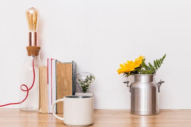 Tazza di fiori in latta libri e lampada sul tavolo Foto Gratuite