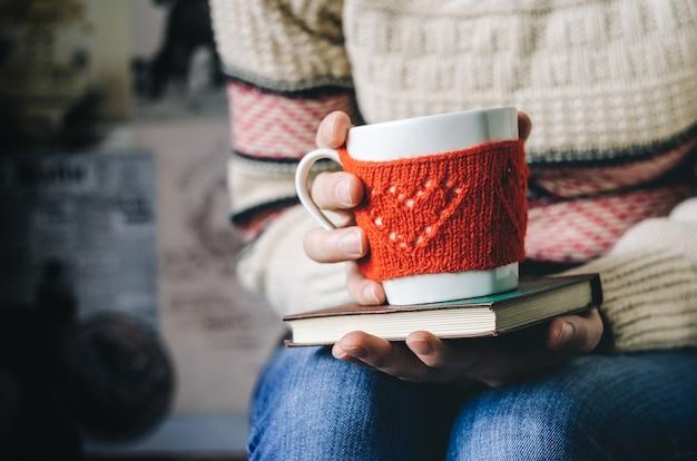 Tazza di lana lavorata a maglia rossa con motivo a cuore in mani femminili. Foto Premium