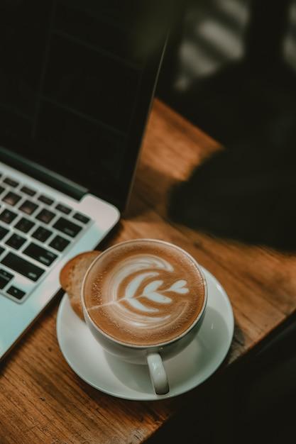 Tazza di latte art accanto a un computer portatile Foto Gratuite