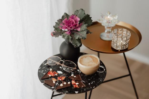 Tazza di latte tè e occhiali da vista su un tavolo nero accanto a una tenda Foto Gratuite