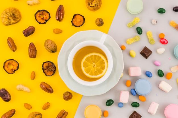 Tazza di tè al limone con frutta secca e caramelle su doppio sfondo giallo e bianco Foto Gratuite