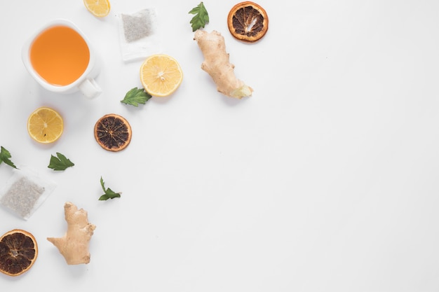 Tazza di tè allo zenzero; fetta di limone; pompelmo secco; erbe e bustine di tè su sfondo bianco Foto Gratuite