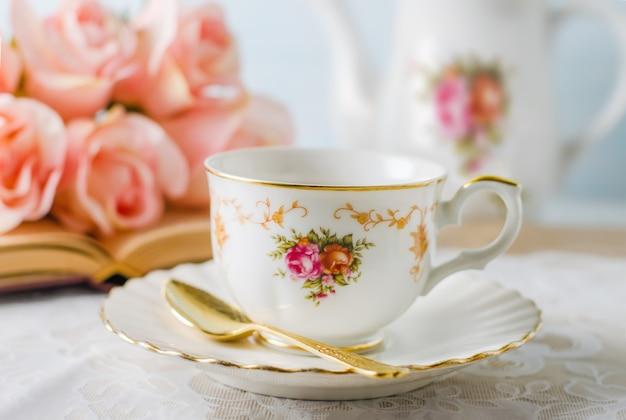 Tazza di tè con libro, teiera e fiori rose su blu Foto Premium