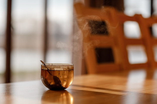 Tazza di tè con vapore sulla tavola di legno nel salone. messa a fuoco selettiva Foto Premium