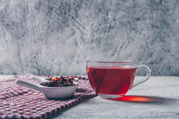 Tazza di tè con vista laterale di erbe di tè su uno sfondo grigio con texture Foto Gratuite