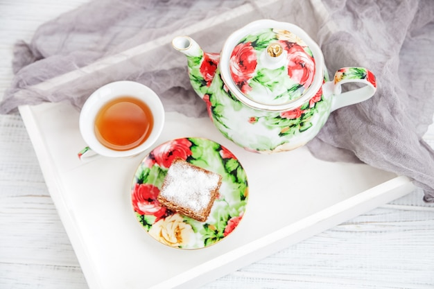 Tazza di tè e fetta di torta su un vassoio di legno. festa estiva. Foto Premium
