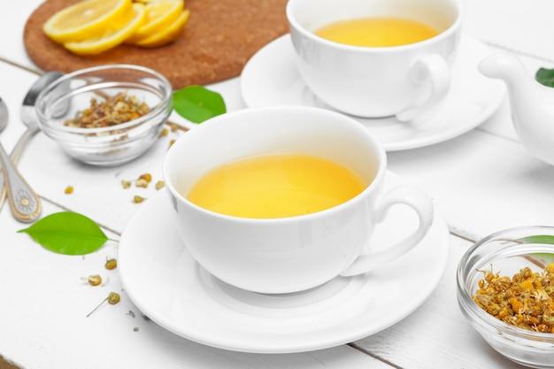 Tazza di tè e foglie di tè sulla tavola di legno bianca. avvicinamento. Foto Premium