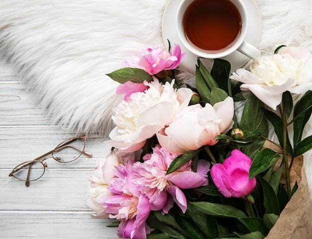 Tazza di tè e peonie rosa Foto Premium