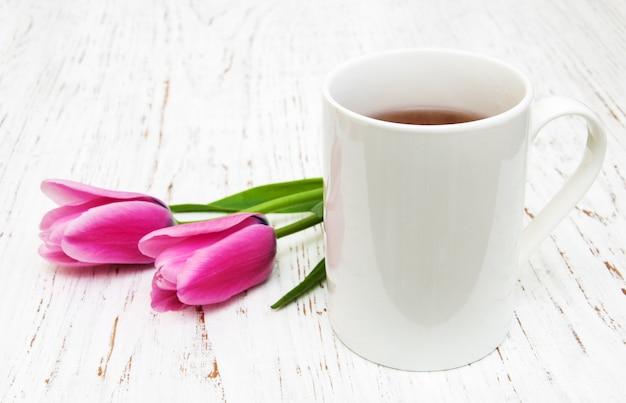 Tazza di tè e tulipani rosa Foto Premium