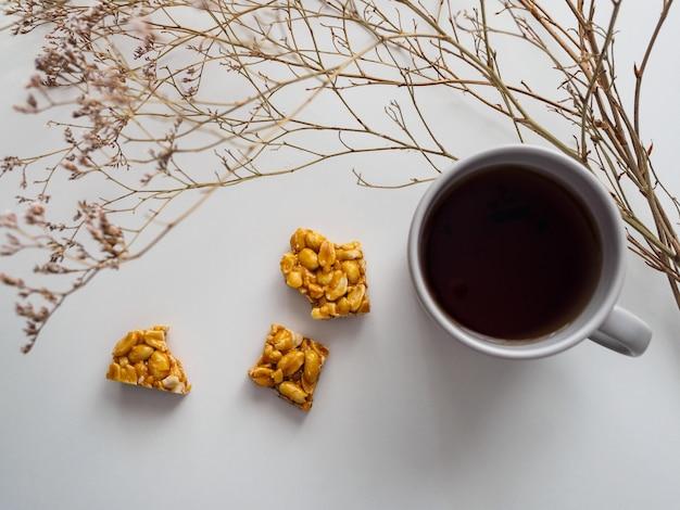 Tazza di tè, kozinak dell'arachide e fiori secchi su un bianco. Foto Premium