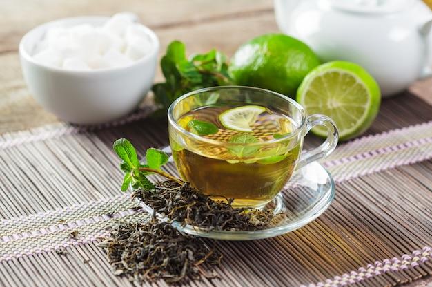Tazza di tè nero con foglie di menta su un tavolo di legno Foto Premium