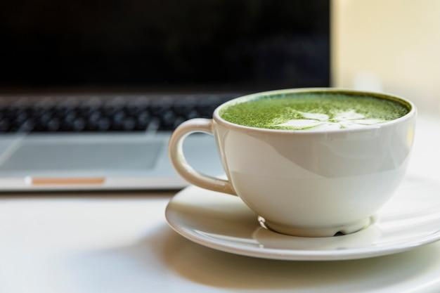Tazza di tè verde giapponese tradizionale di matcha vicino al computer portatile sullo scrittorio Foto Gratuite