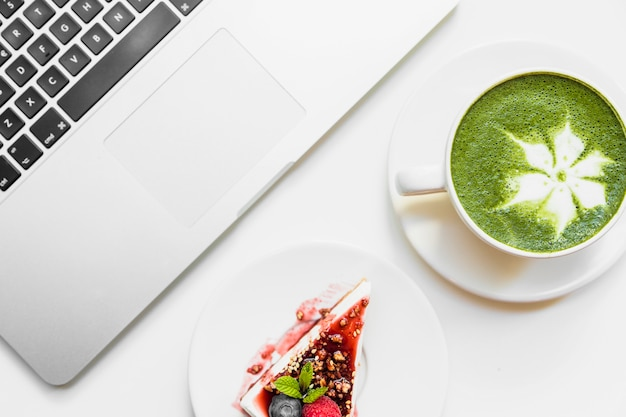 Tazza di tè verde matcha; cheesecake e laptop su sfondo bianco Foto Gratuite