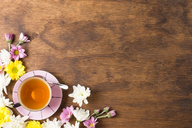 Tazza di tisana e bei fiori sull'angolo dello sfondo in legno Foto Gratuite