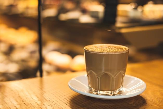Tazza di vetro delizioso gustoso latte con piattino sul tavolo Foto Gratuite
