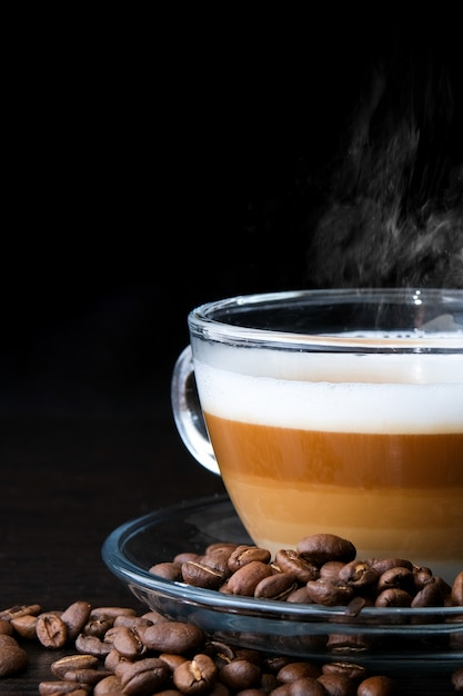 Tazza di vetro trasparente cappuccino con strati visibili di caffè, latte e schiuma e fagioli sul nero Foto Premium