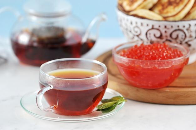 Tazza di vetro trasparente con tè nero e menta su pancake e caviale Foto Premium