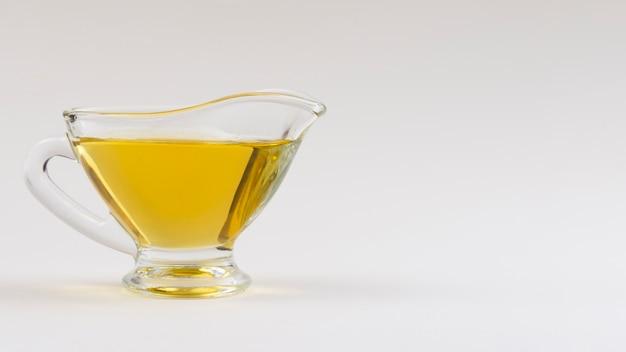 Tazza di vista frontale con olio d'oliva sul tavolo Foto Gratuite