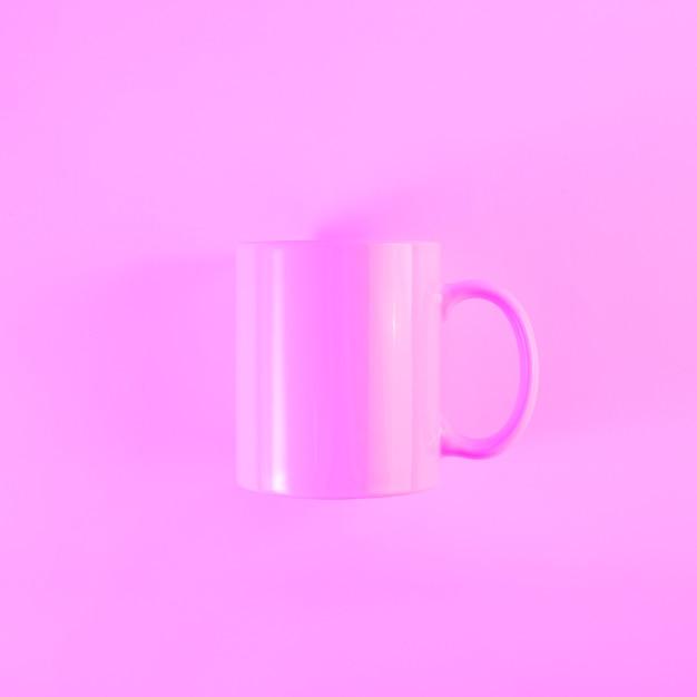 Tazza dipinta di rosa con manico su sfondo colorato Foto Gratuite