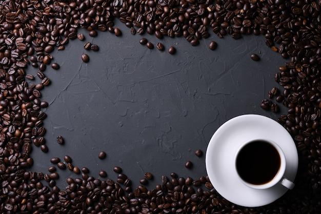 Tazza e fagioli di caffè sul vecchio beton grigio della cucina, tavola della roccia. vista dall'alto con copyspace per il testo Foto Premium