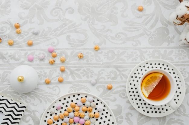 Tazza e piattino di tè del limone dello zenzero con le caramelle variopinte sulla carta da parati Foto Gratuite