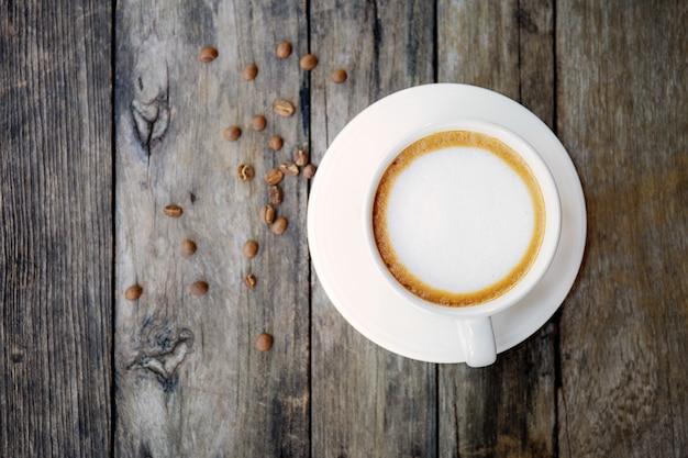 Tazza e seme di caffè su legno. Foto Premium