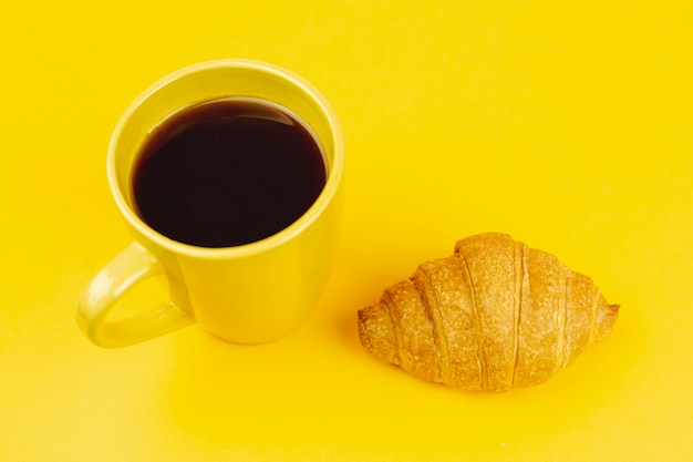 Tazza gialla con caffè e cornetto su uno sfondo giallo Foto Gratuite