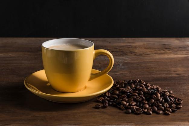 Tazza gialla e chicchi di caffè Foto Gratuite
