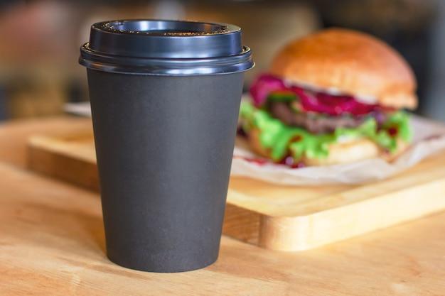 Tazza nera con caffè per andare su fondo con hamburger, mock up Foto Premium