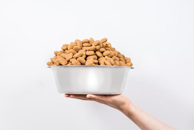 Tazza piena con uno scorrevole di alimento per animali domestici asciutto isolato su fondo bianco Foto Premium