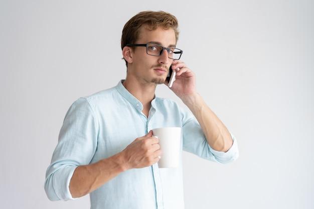 Tazza seria della tenuta dell'uomo e parlare sullo smartphone Foto Gratuite