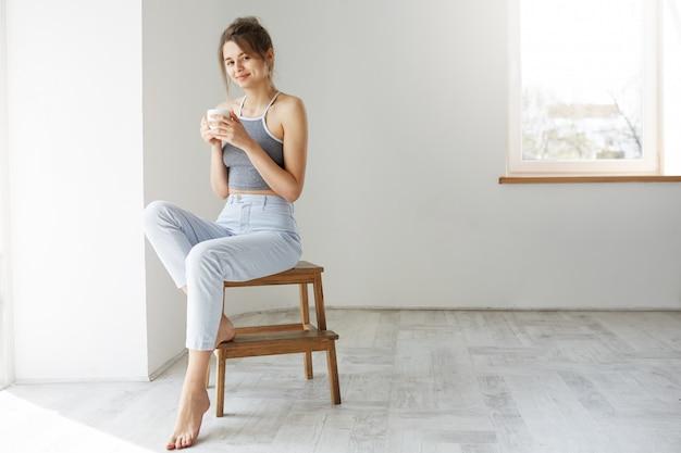Tazza sorridente della tenuta della giovane donna castana tenera che si siede sulla sedia sopra la parete bianca nelle prime ore del mattino. Foto Gratuite